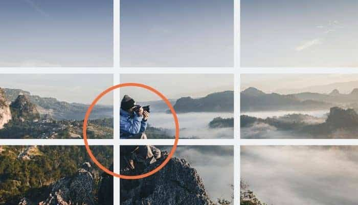 Man sitting on a mountain and holding a camera with a 3x3 grid.