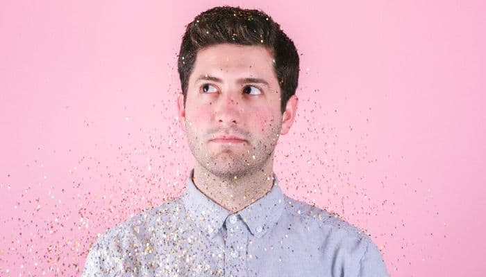 Person with a pink background and confetti.