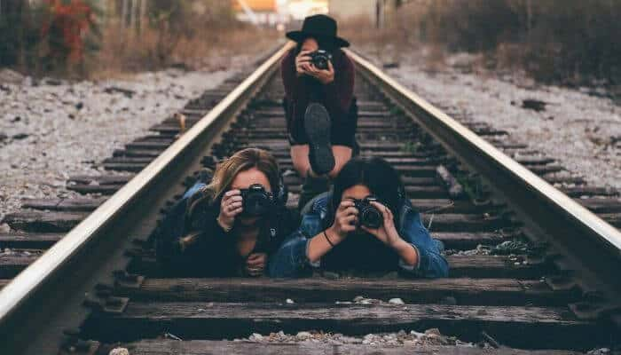 3 photographers on a railroad track.