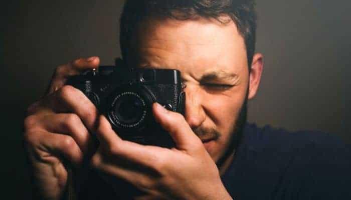 Person holding black camera.