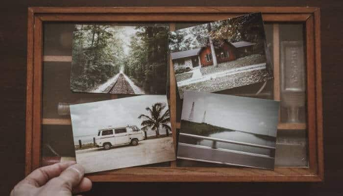 Person holding printed photos.