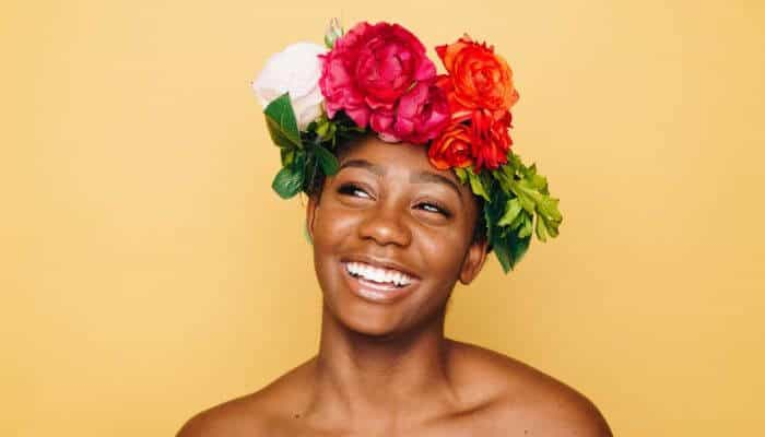 Woman smiling with flowers on her head.