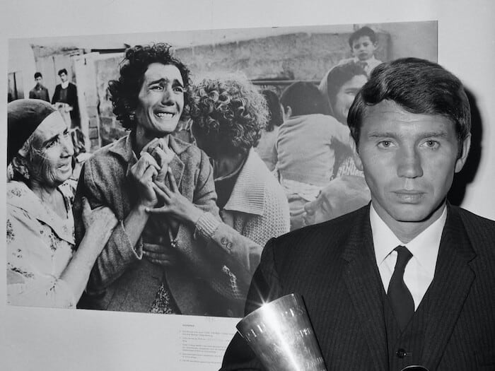 Don McCullin holding a trophy while standing in front of a poster.