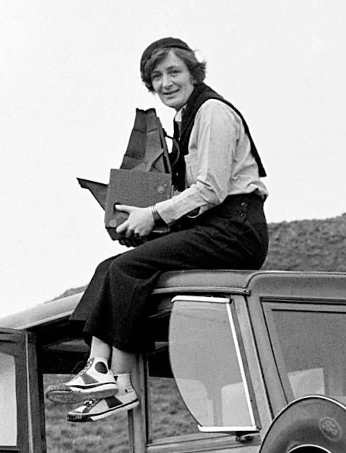 Grayscale portrait of Dorothea Lange sitting on the top of a car.
