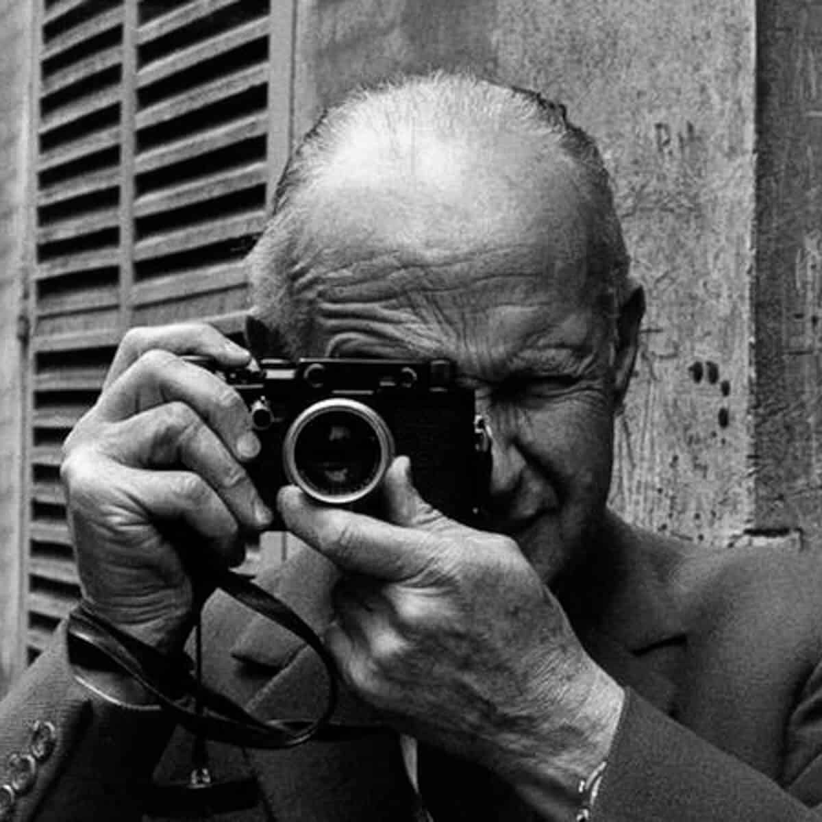 Grayscale of a man taking a photo.