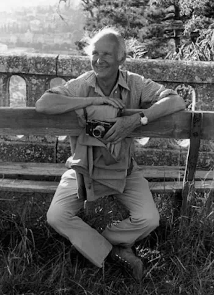 Grayscale portrait of Henri Cartier-Bresson holding a camera.