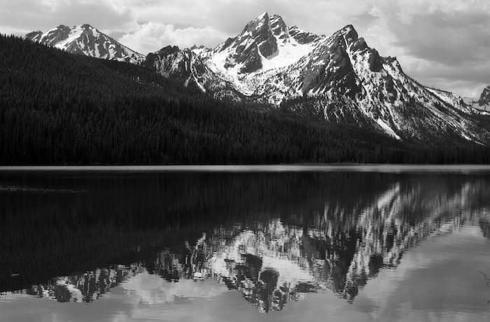 Grayscale of a mountain and its reflection on a lake.