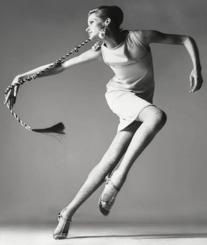 Grayscale of a woman leaping.