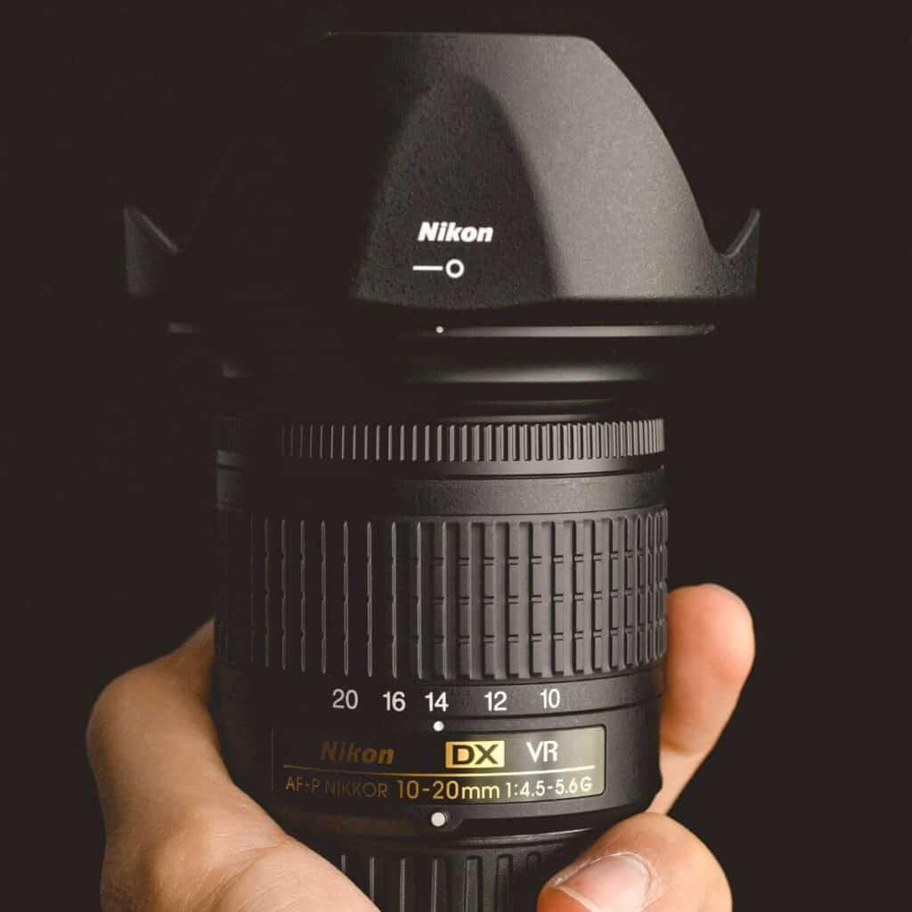 Hand holding a camera lens.