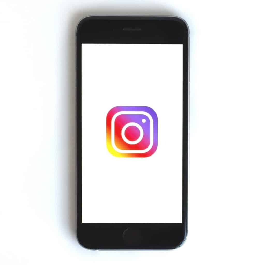 Phone showing Instagram logo on screen.