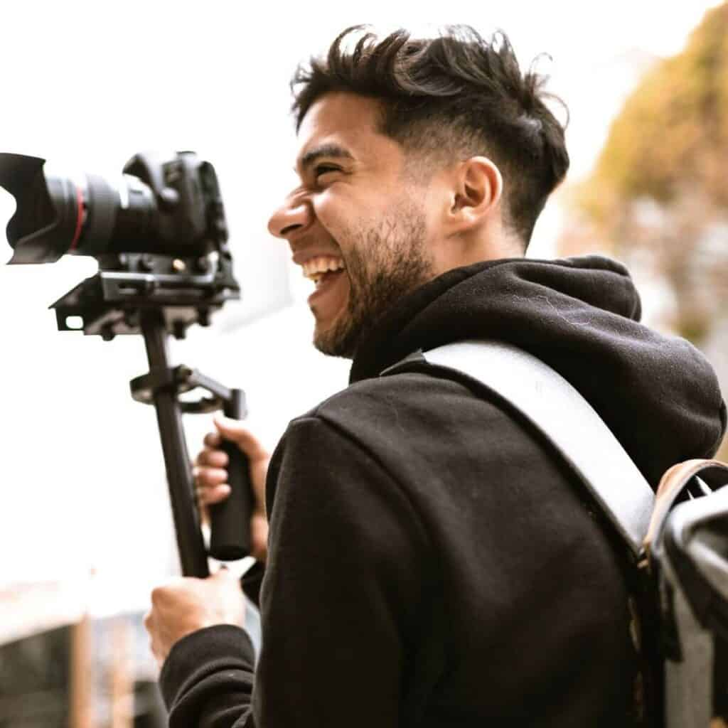 Person wearing a backpack and holding a monopod.