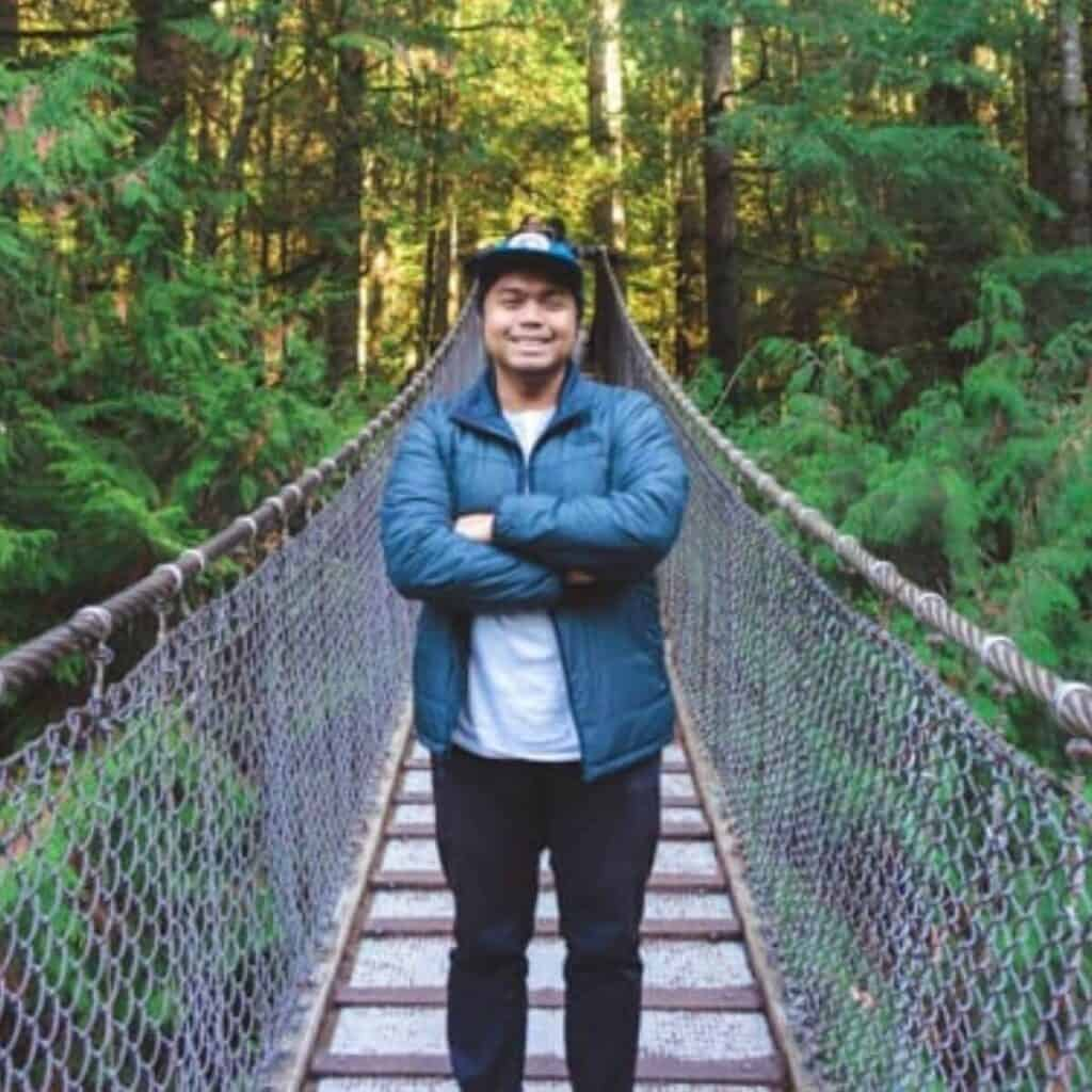 Person standing on a bridge in the forest.
