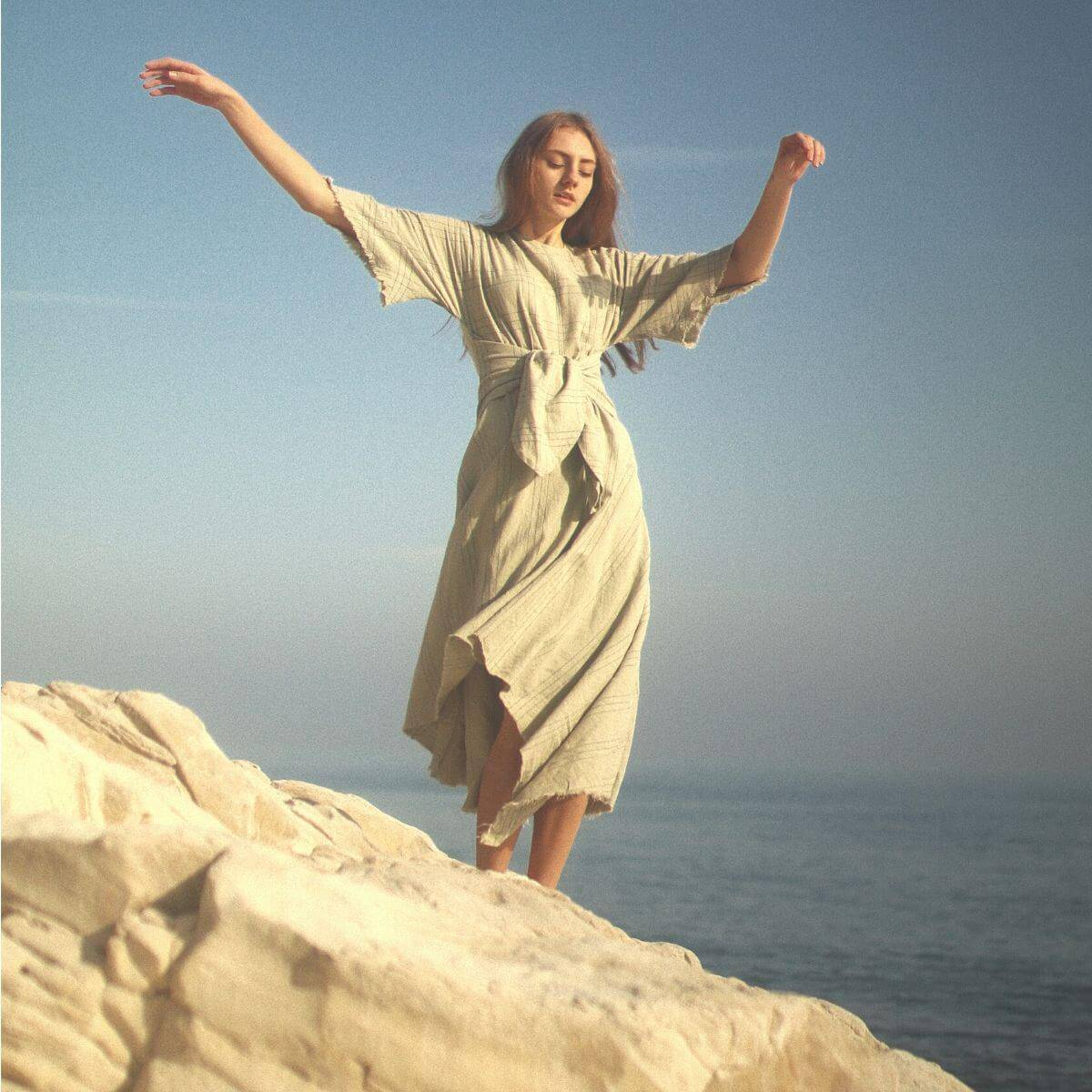 Person standing on a rock with arms in the air.
