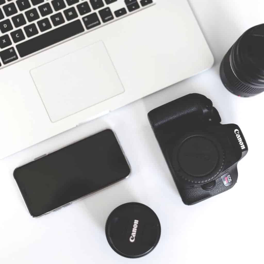 Flatlay of camera, laptop, lenses, and phone.