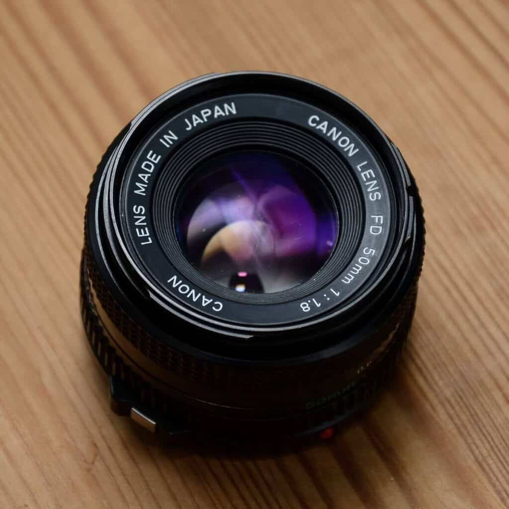 Canon 50mm lens on a wooden table.