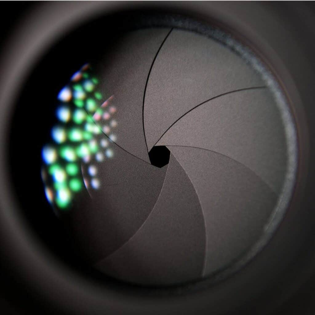 Close-up of a camera lens showing the aperture.