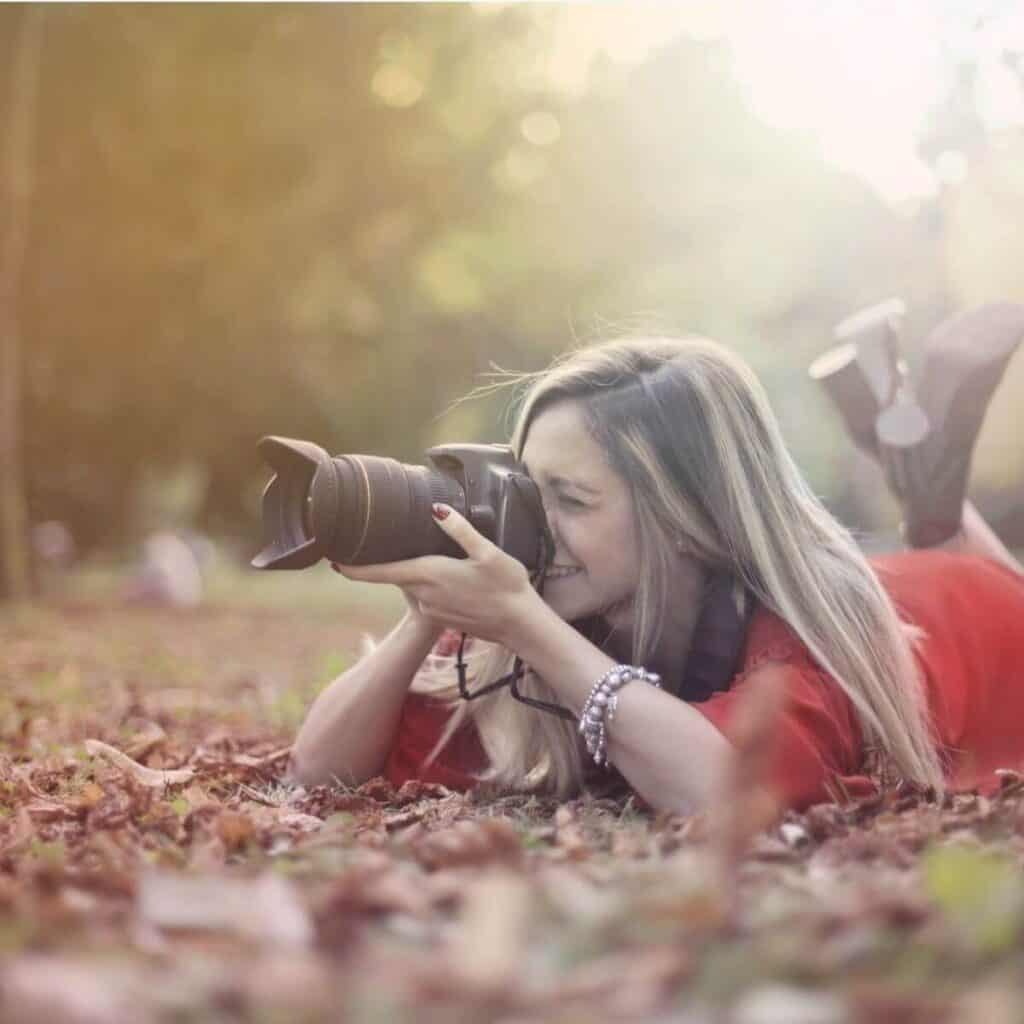 Photographer lying on the ground while taking a photo.