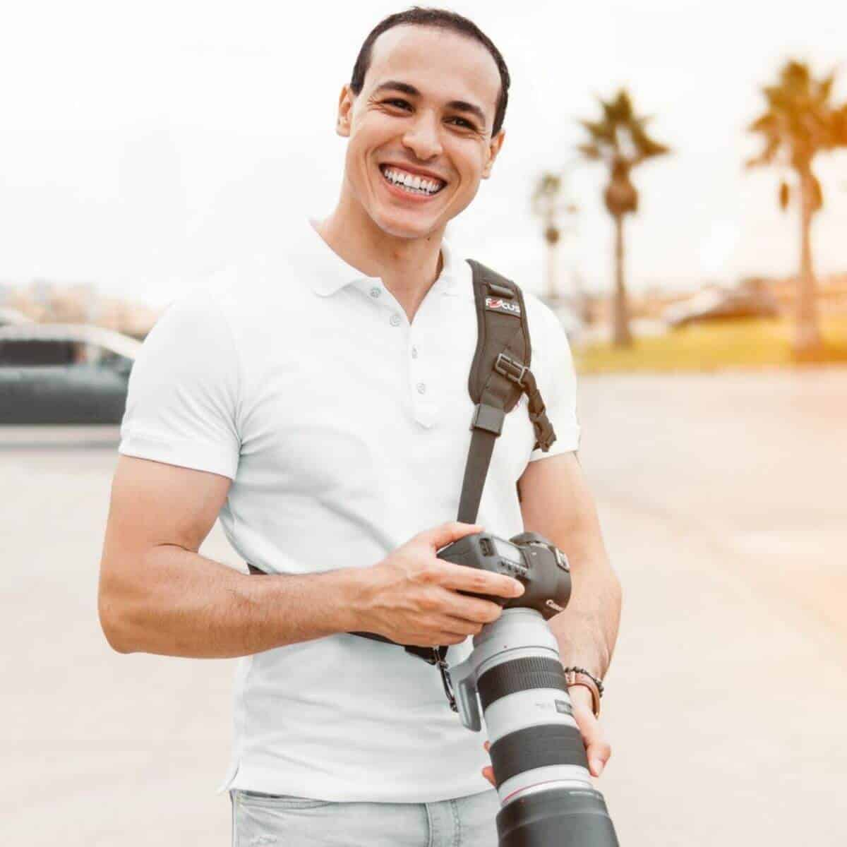 Photographer smiling while holding a camera.