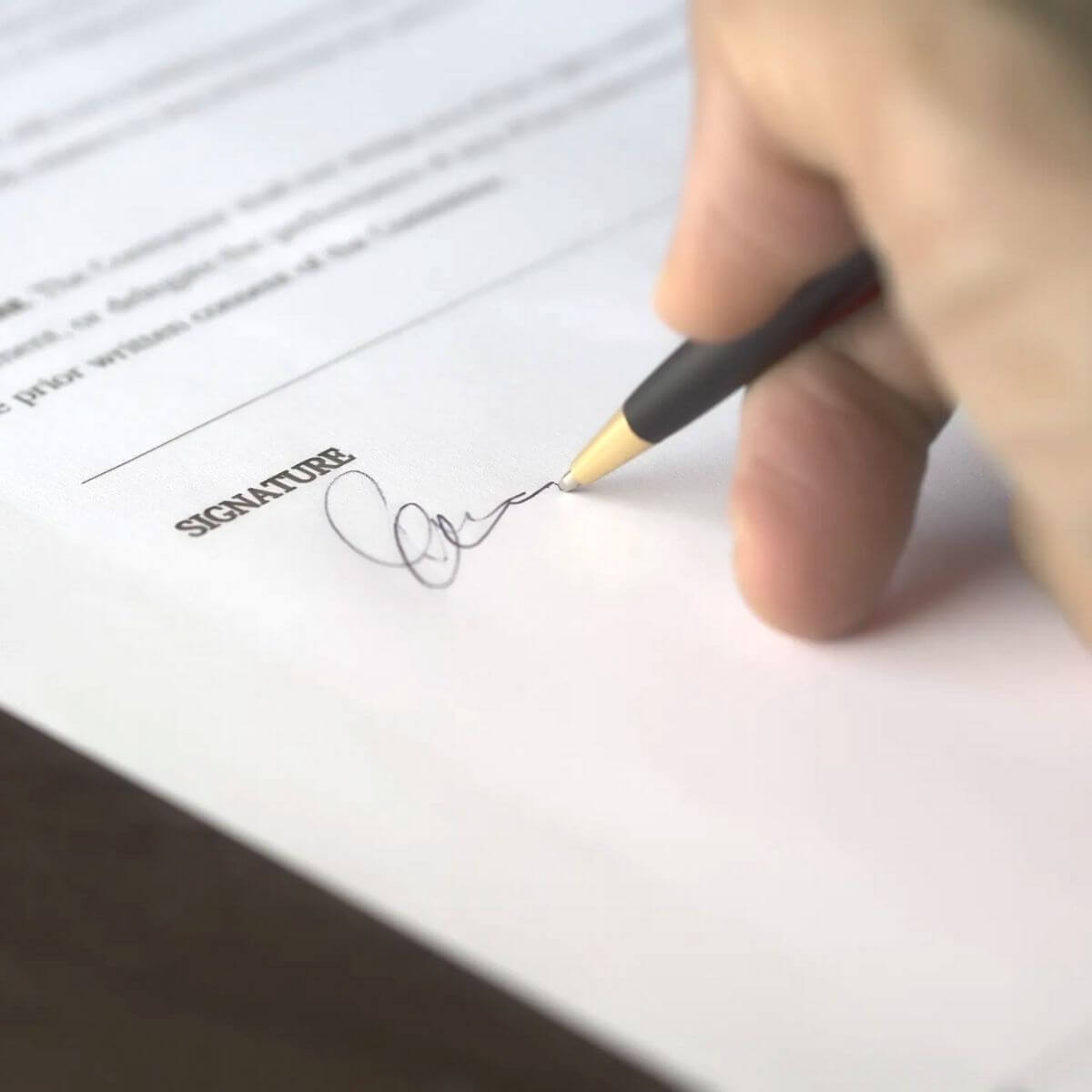 Close-up of a person signing a document.