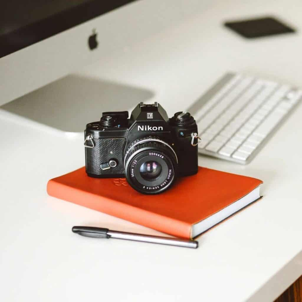 Camera on a notebook with a computer behind it.