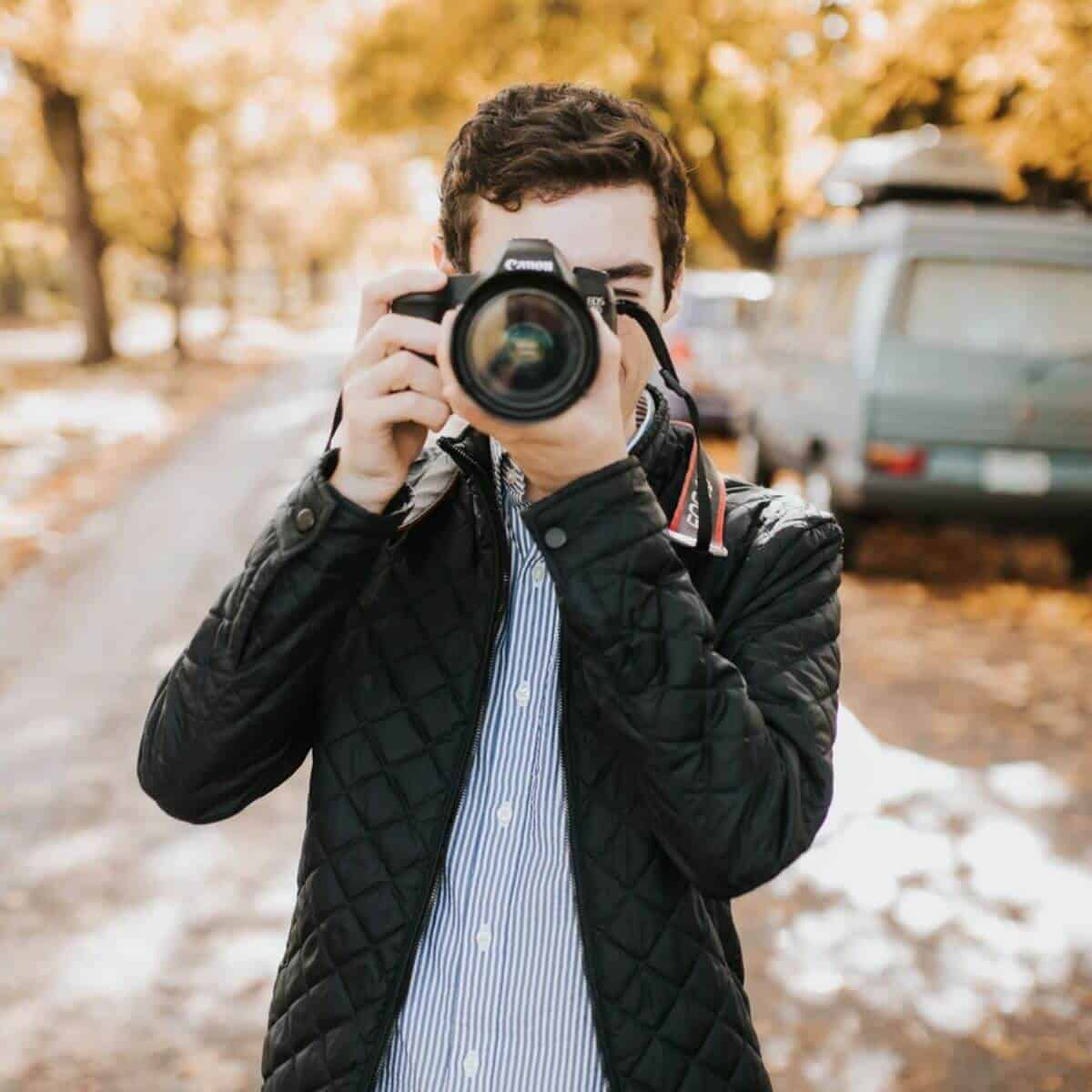 Photographer taking a photo outdoors during autumn.