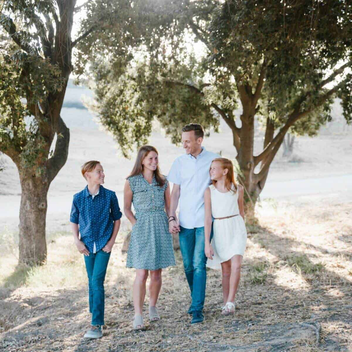 Family of four walking in front of a tree.