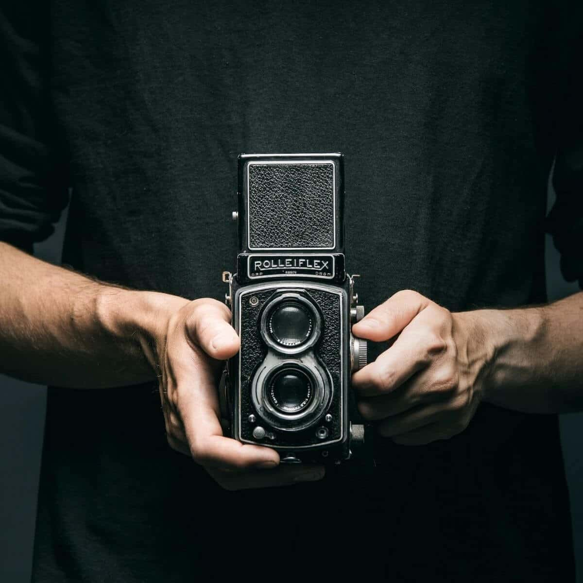 Close-up of a person holding a Rolleiflex camera.