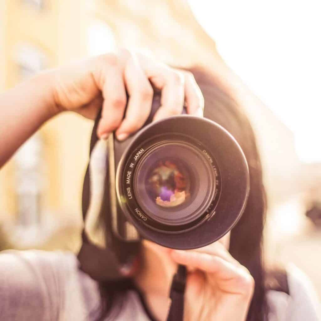 Selective focus on a camera lens while a person is taking a photo in the city.