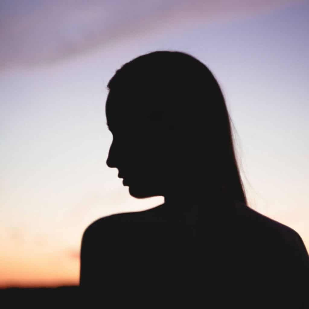 Silhouette of a person looking to the left during a sunset.