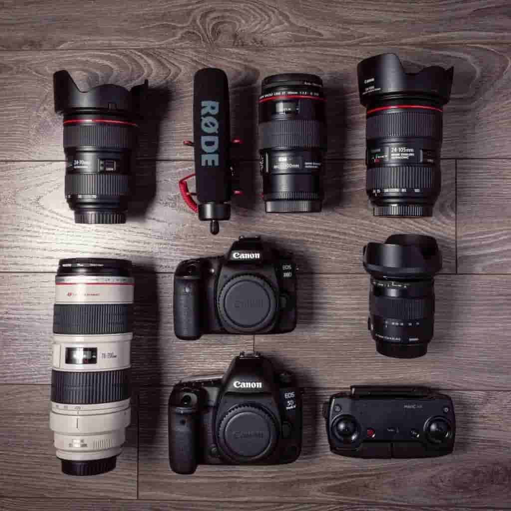 Flatlay of cameras, lenses, microphones, and a remote control.