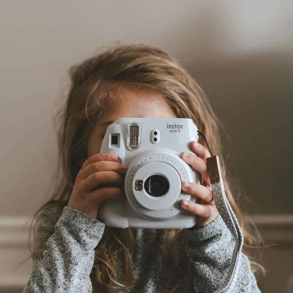 Kid holding a polaroid camera near a wall indoors.