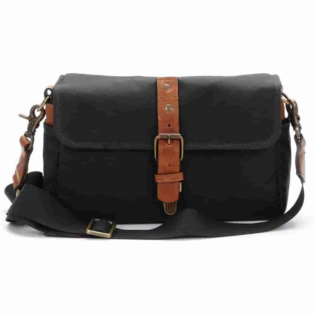 Black waxed canvas messenger bag with brown leather accents.