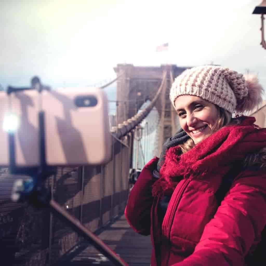 Person on a bridge using a selfie stick to take a self-portrait.