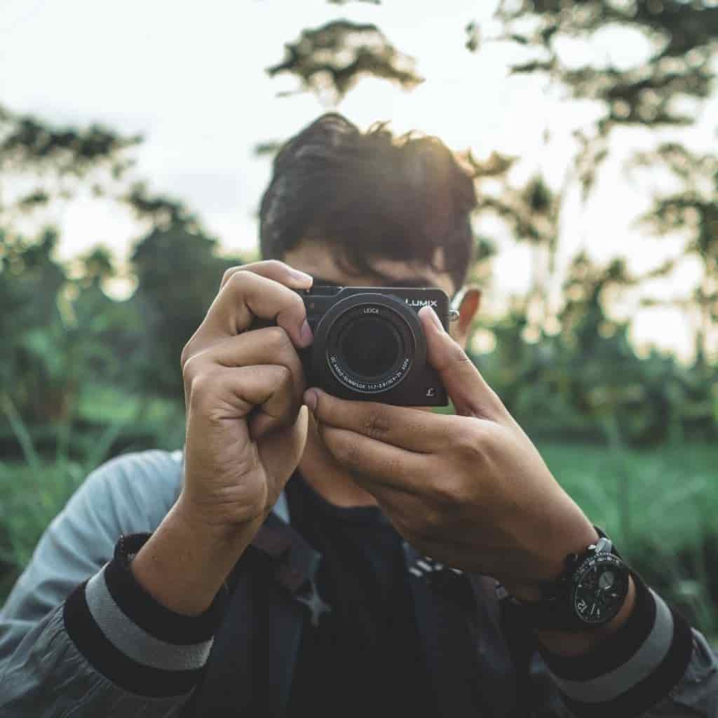 Photographer using a compact camera in a field of grass.