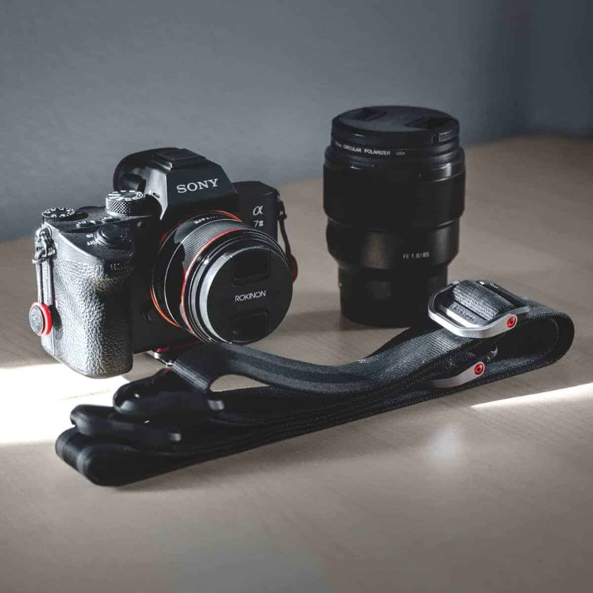 Camera, lens, and strap on a table.