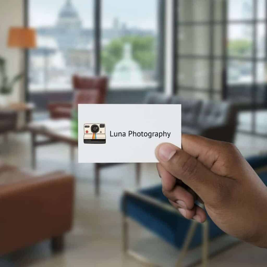 Person's hand holding a photography business card.