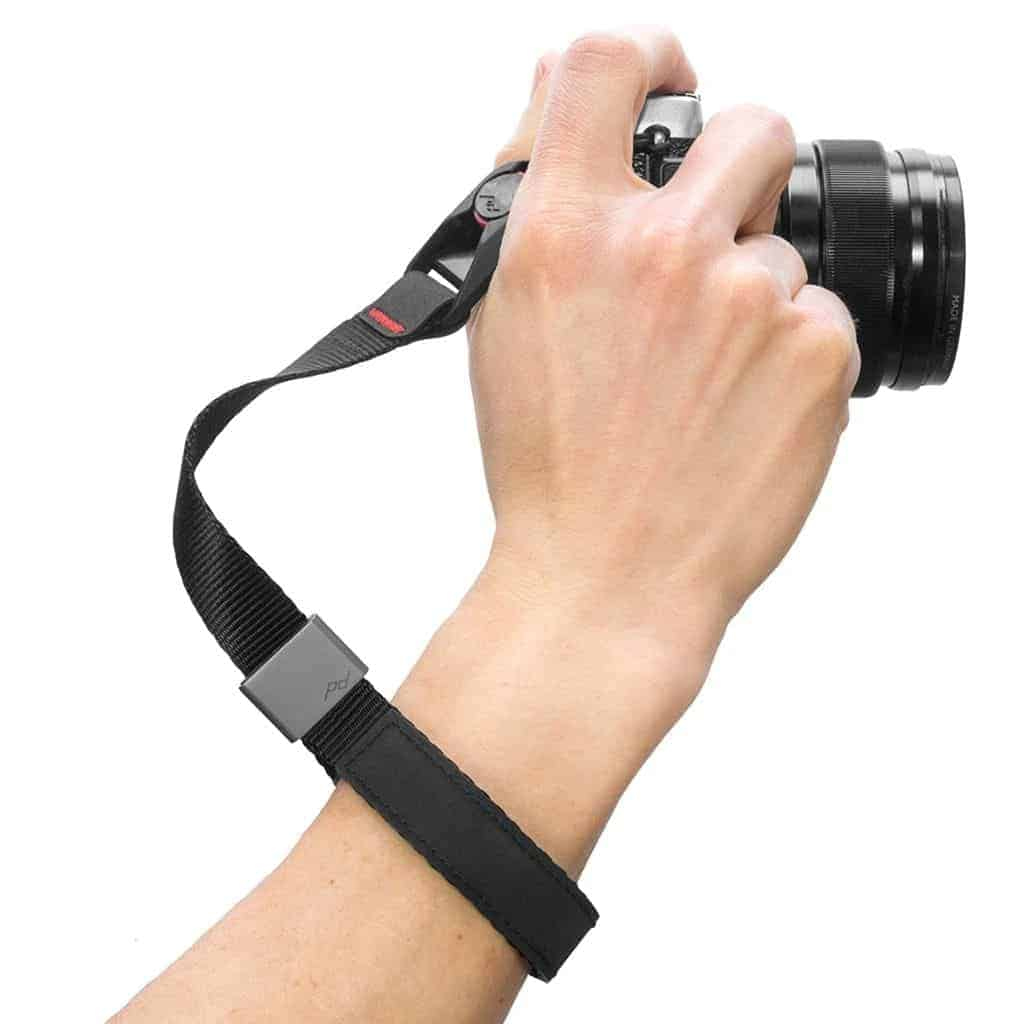 Close-up of a persons hand with a camera strap cuff on.