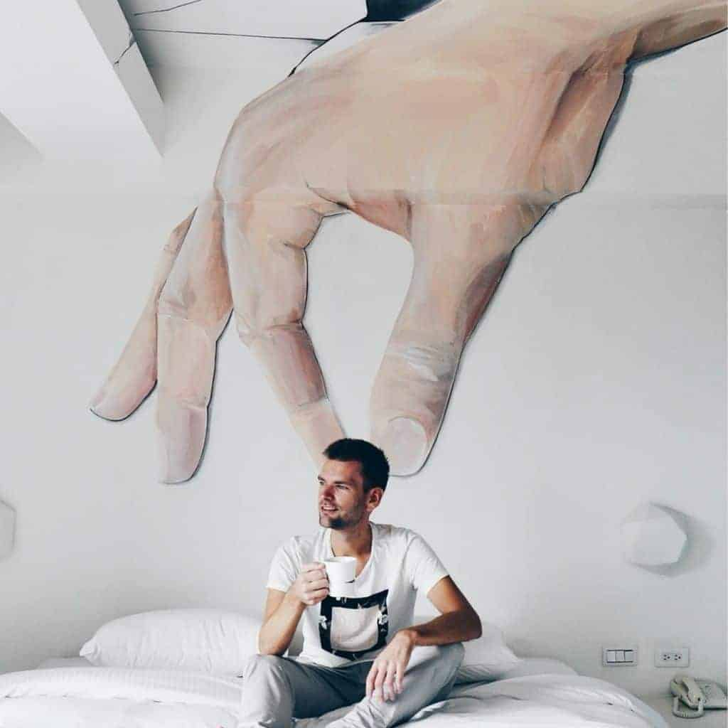 Forced perspective of a big hand grabbing a person's head.