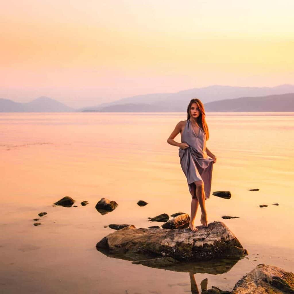Person standing on a rock in the water during a sunset.