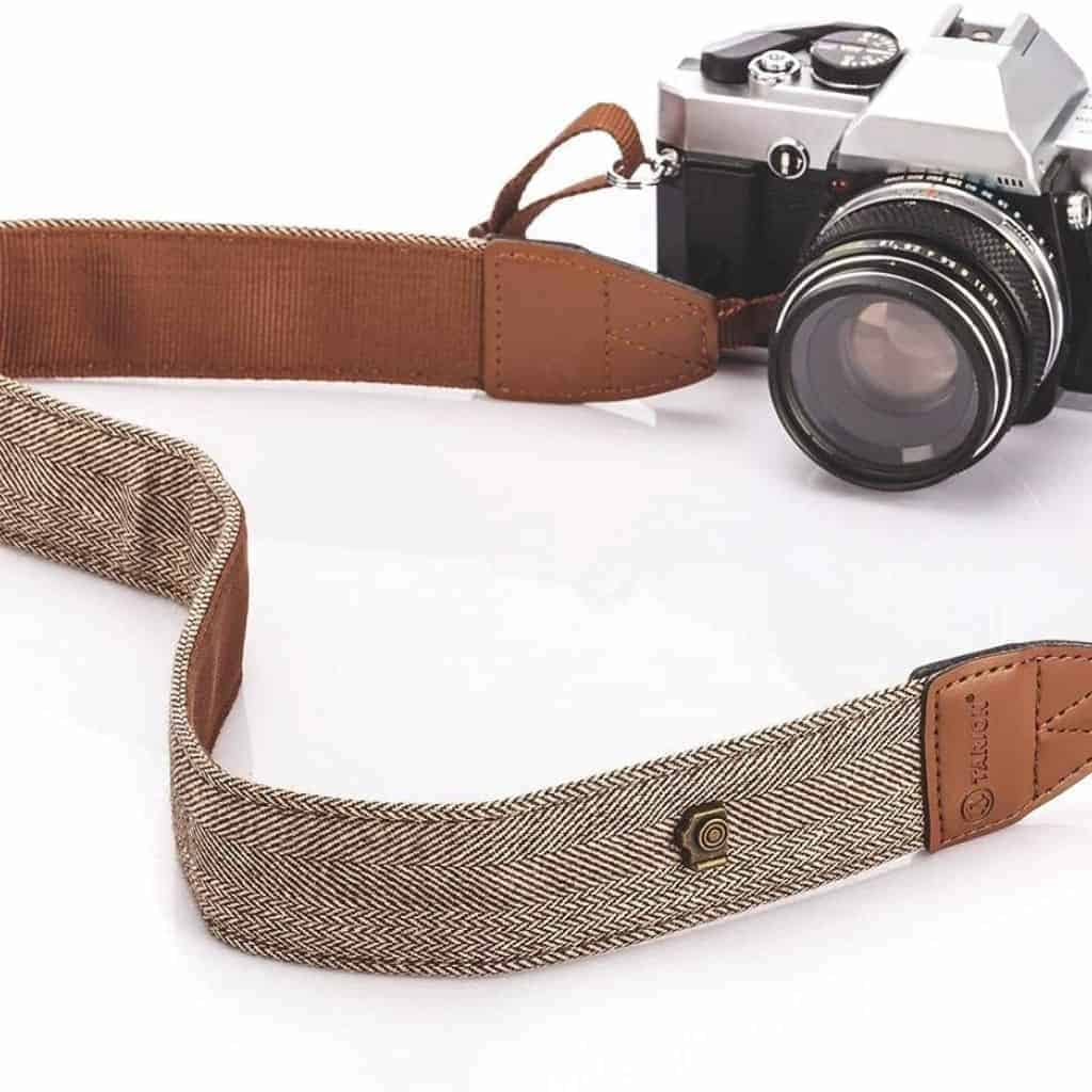 Leather and herringbone camera strap connected to a camera.