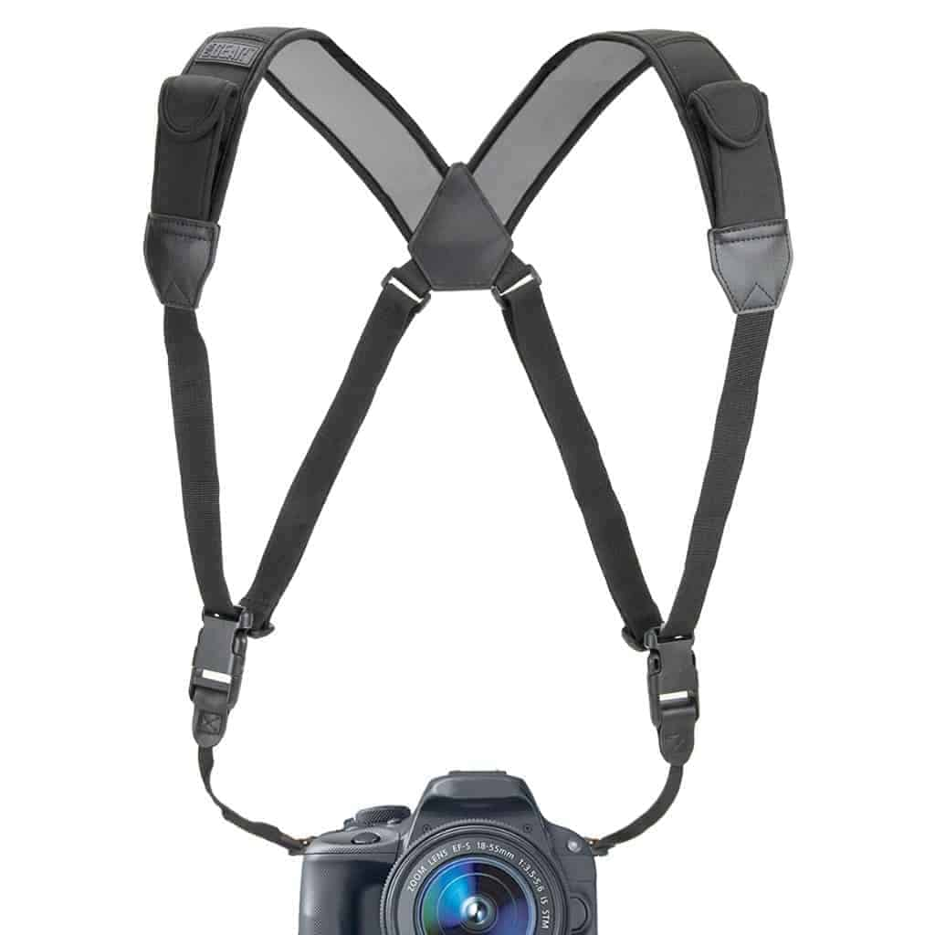 Black camera strap harness with a camera attached to it.