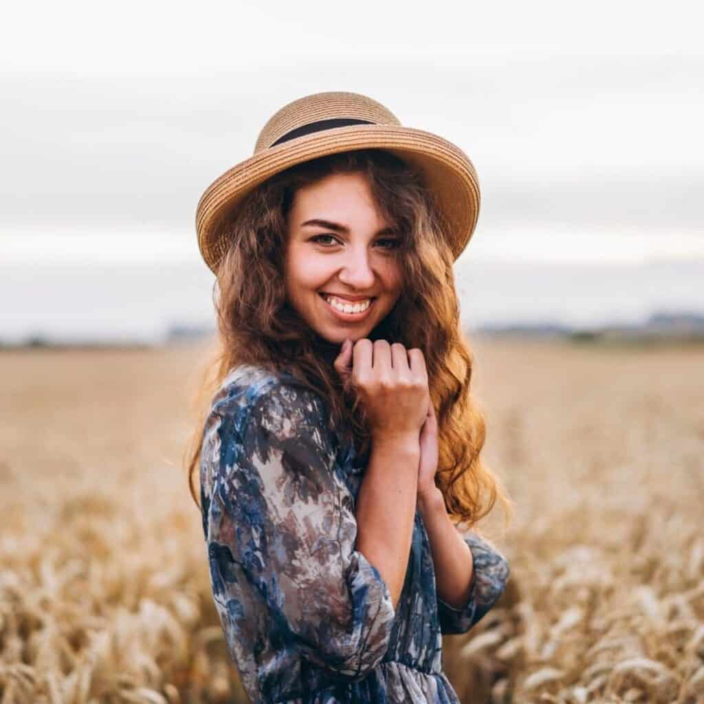 Woman wearing a hat and standing in a field.