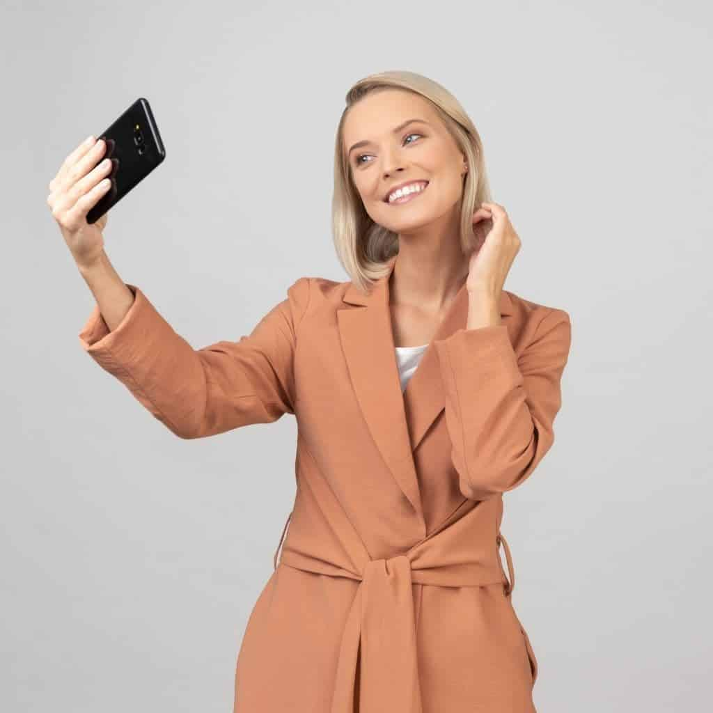 Person wearing an overcoat and taking a selfie inside.