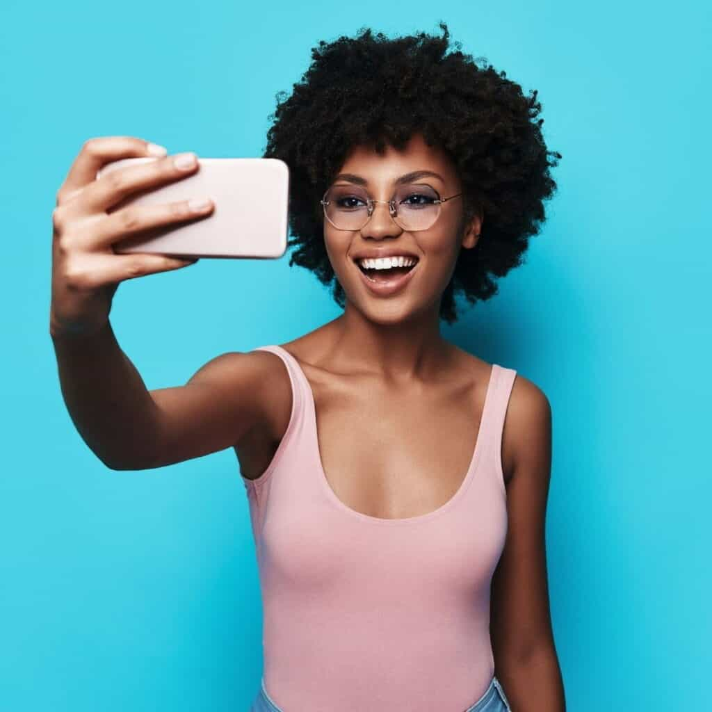 Woman wearing glasses and taking a selfie with a blue background.